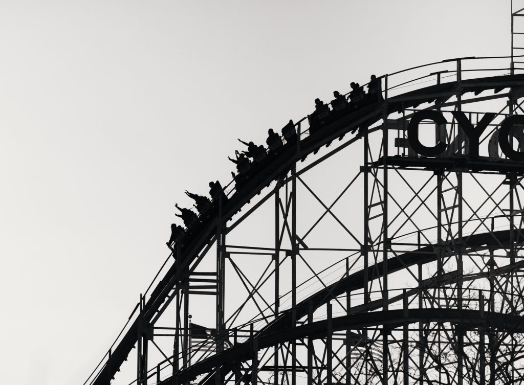 Silhouette of a car on a roller coaster about to go down a large hill