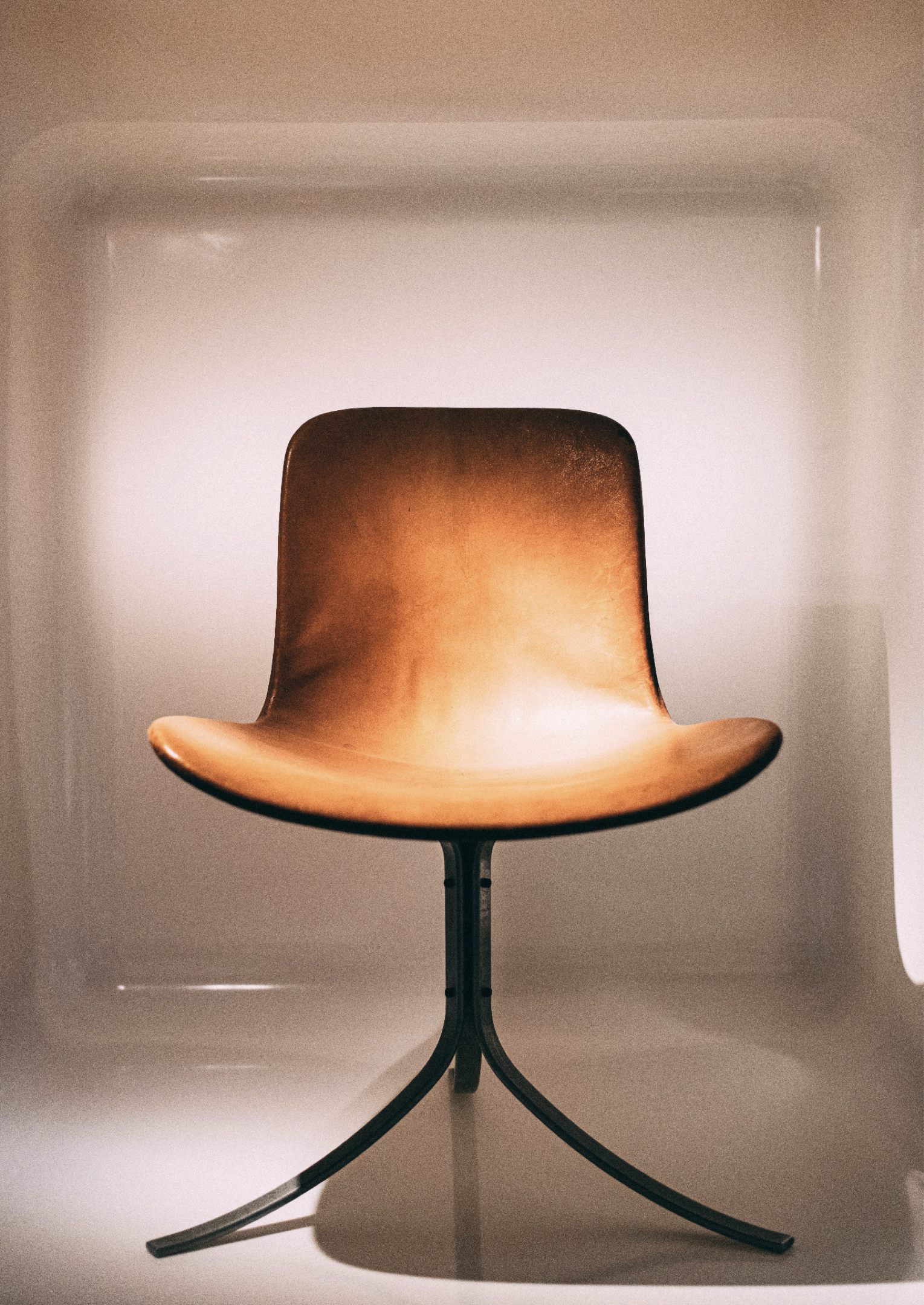 A brown leather black chair with a seamless back facing directly at the camera, with three curved black legs.